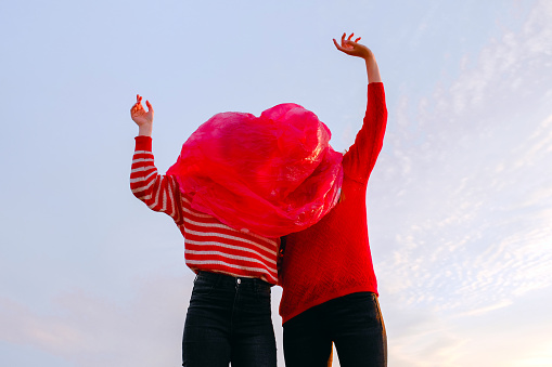 Two figures wearing a red and red plastic bag on the head against the sky - gettyimageskorea