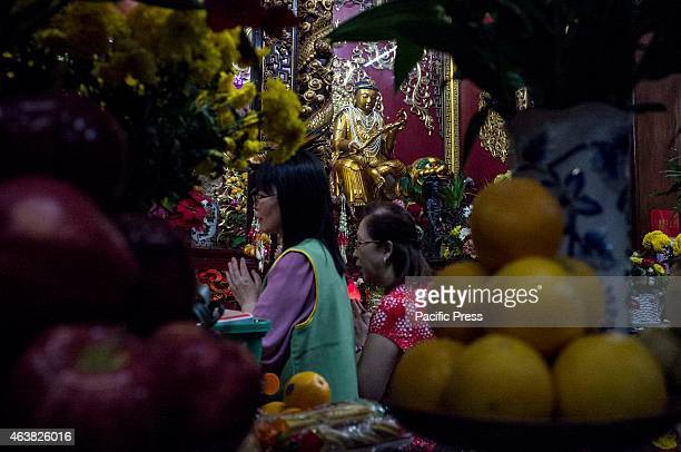 Two FilipinoChinese women solemnly say their prayers in front of an altar in one of the Seng Guan temple shrines