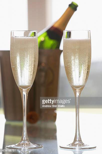 Two filled champagne flutes and bottle chilling