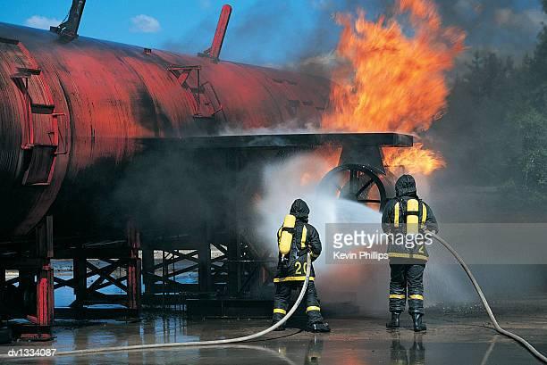 two fire fighters extinguishing a blazing pipeline at an oil refinery - vlak naast stockfoto's en -beelden