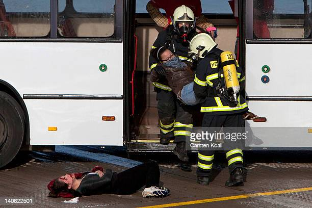 Two firefighters carry a woman off a bus during an emergency drill at new Berlin Brandenburg Airport on March 3 2012 in Berlin Germany At the...