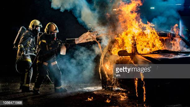 two firefighters extinguishing a burning car with foam - burning stock pictures, royalty-free photos & images