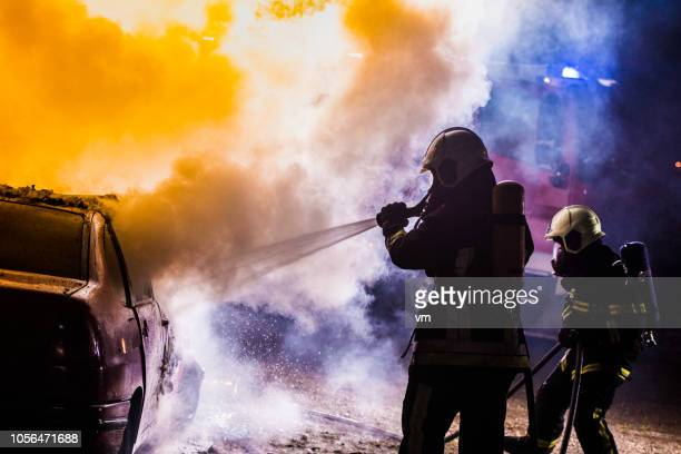 two firefighters extinguishing a burning car with water - burning stock pictures, royalty-free photos & images