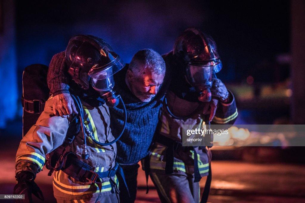 Dos bomberos ayudando a la víctima : Foto de stock