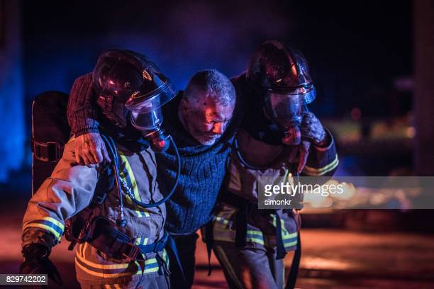 two firefighters helping victim - rescue worker stock pictures, royalty-free photos & images