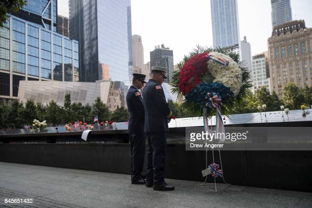 Two firefighters pause and pay their respects at the North pool during a commemoration ceremony for the victims of the September 11 terrorist attacks...