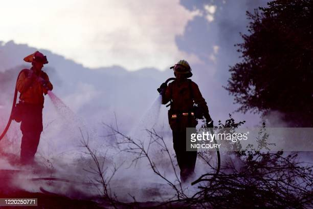 Two firefighters put out hotspots of the Avila Fire on the on-ramp to Highway 101 in Pismo Beach, San Luis Obispo County, California, June 15, 2020....