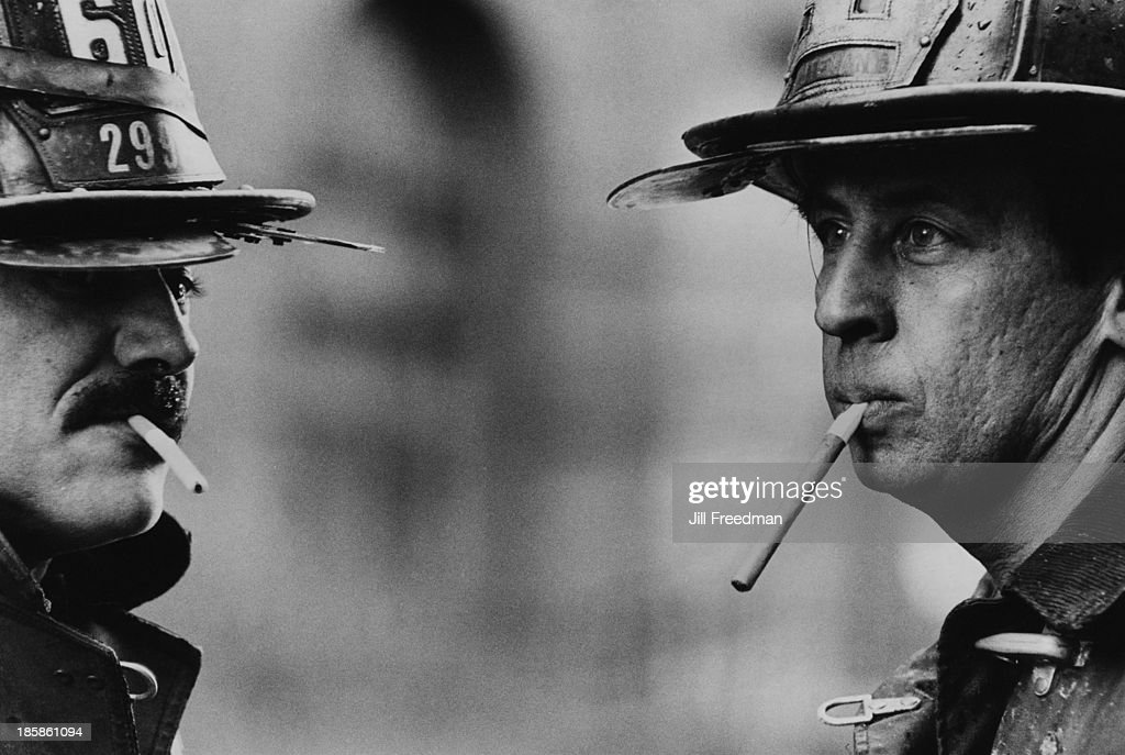 Two firefighters relax with a cigarette after a call-out in New York City, circa 1976.