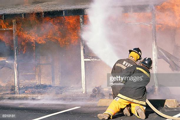 Two firefighters spraying burning building