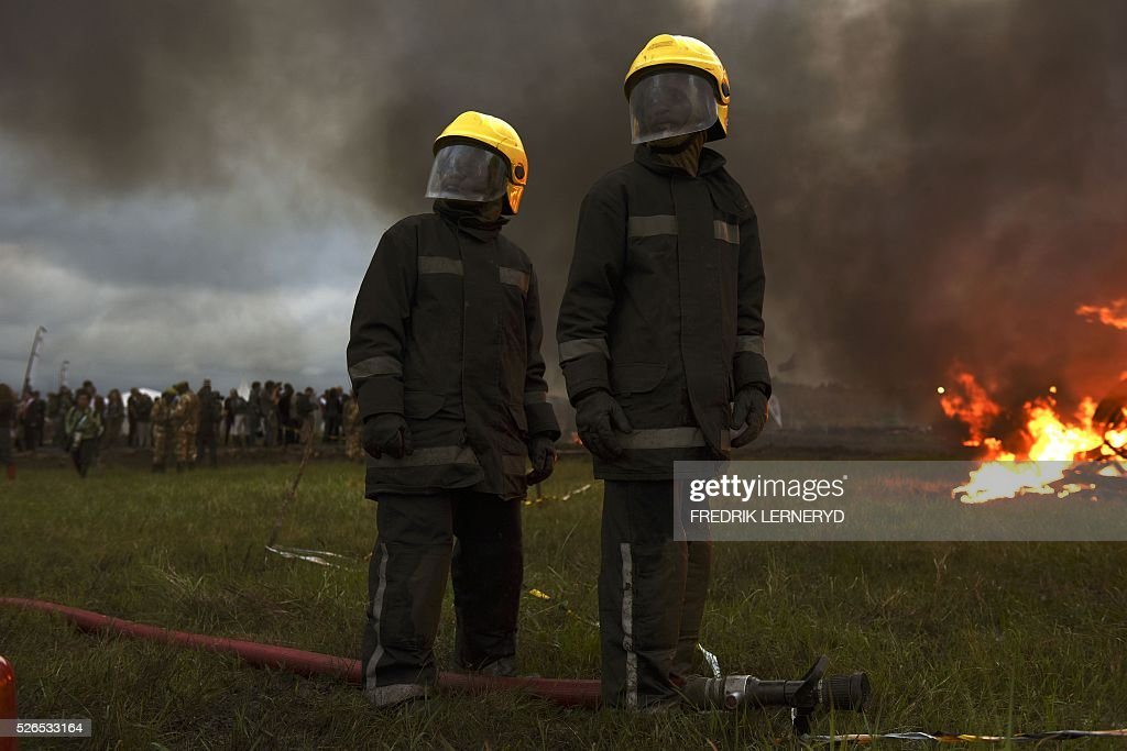Two firefighters stand next to eleven burning stacks of elephant tusks ivory and rhinoceros horns at Nairobi National Park on April 30, 2016. Kenyan President Uhuru Kenyatta set fire on April 30, 2016, to the world's biggest ivory bonfire, after demanding a total ban on trade in tusks and horns to end 'murderous' trafficking and prevent the extinction of elephants in the wild. / AFP / FREDRIK
