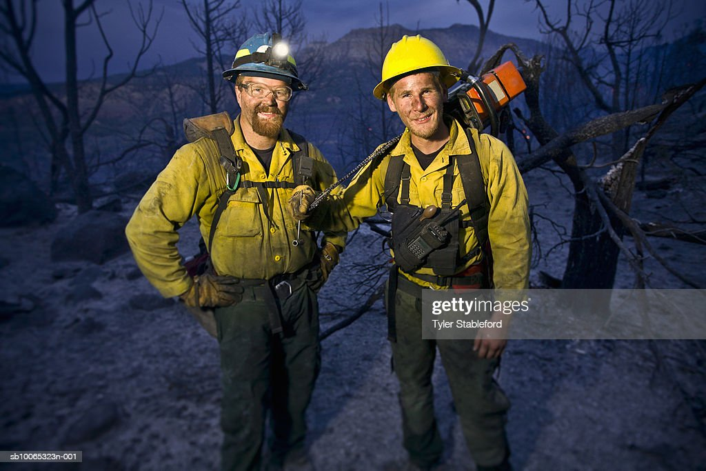 Two fire-fighters standing together in burnt forest, portrait : Foto stock