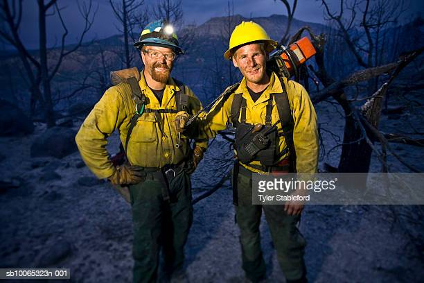 Two fire-fighters standing together in burnt forest, portrait