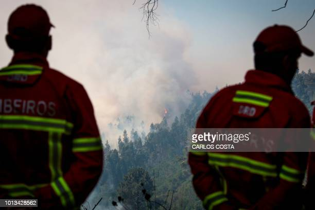 Two firefighters watch a wildfire progression close to Monchique in the Portuguese Algarve, on August 8, 2018. - Wildfires scorched across Portugal's...