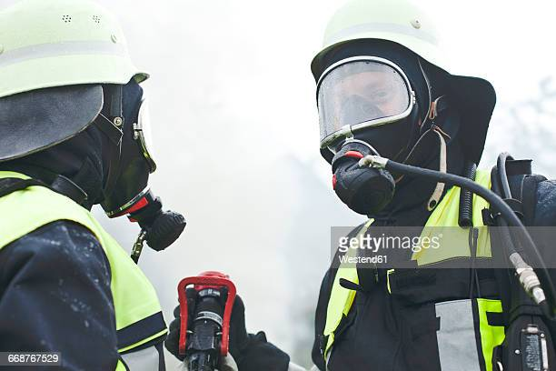 Two firefighters wearing oxygen masks