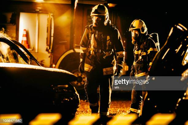 two firefigters walking around the scene after successfully extinguishing a fire - fire protection suit stock photos and pictures