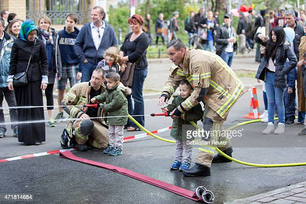 Two firemen play a game with two children at MyFest in BerlinKreuzberg on May 1 2015 in Berlin Germany May Day or International Workers' Day was...