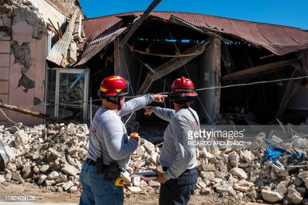 TOPSHOT Two firemen survey a collapsed building after an earthquake hit the island in Guanica Puerto Rico on January 7 2020 A strong earthquake...