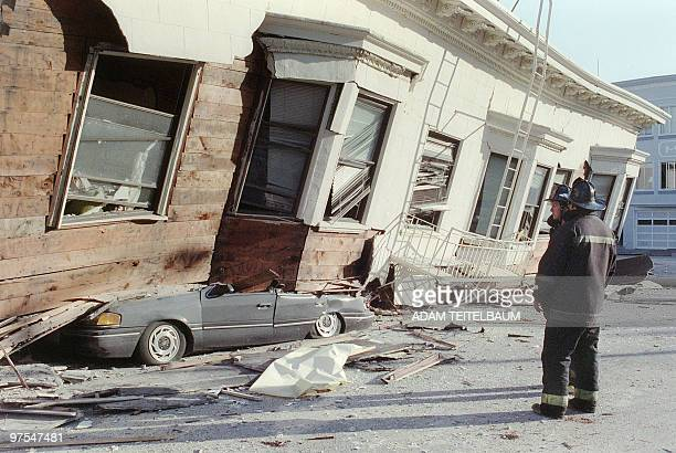 Two firemen watch, in San Francisco, 18 October 1989, a collapsed house that crushed a car in the Marina District, one of the areas worst hit by an...