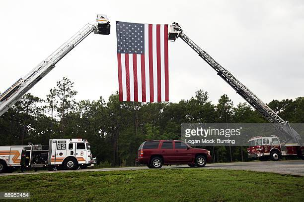 Two firetrucks hold up a giant American Flag outside the funeral of Sgt 1st Class Edward Kramer on July 9 2009 in Wilmington North Carolina Kramer...