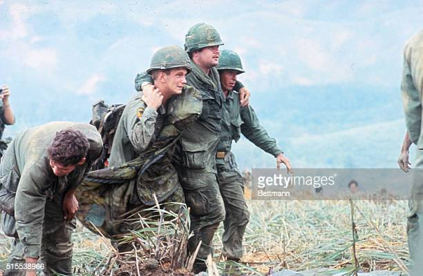 Two First Cavalry men support a wounded third as they advance along Route en route to Khe Sanh