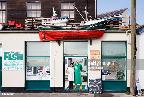 Two fish mongers standing in shop doorway