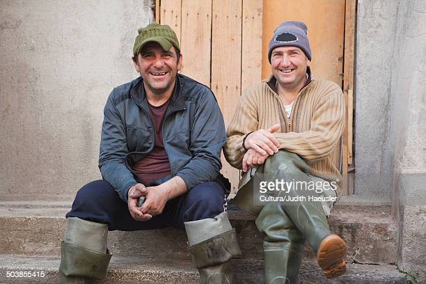 two fisherman sitting on steps, laughing