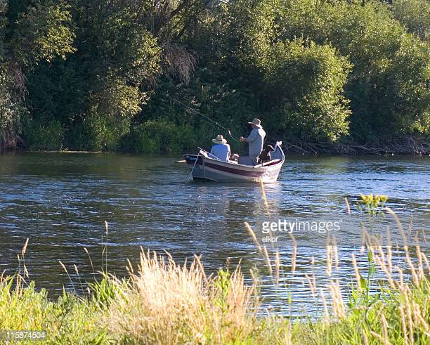 Two fishermen and a dog in fishing boat