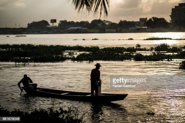 Two fishermen fish at the Ebrie Lagoon on November 28 2017 in Abidjan Ivory Coast