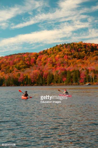 Two fishermen in kayaks make their way on Kettle Pond in Groton Vermont during foliage