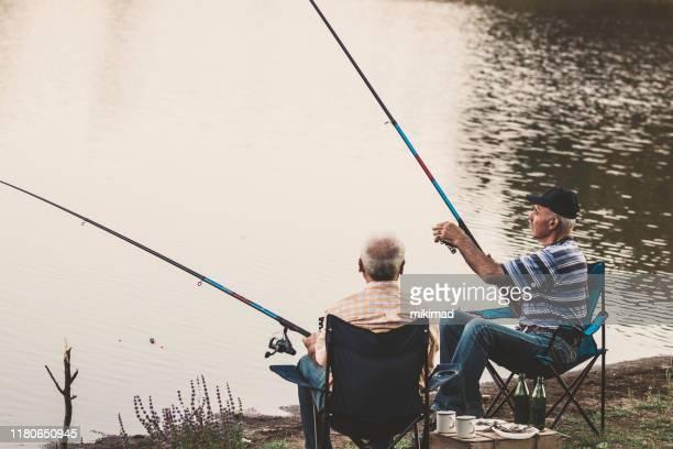 湖に2人の漁師がいるシニアマン釣り。リラックスした時間 - 淡水釣り ストックフォトと画像
