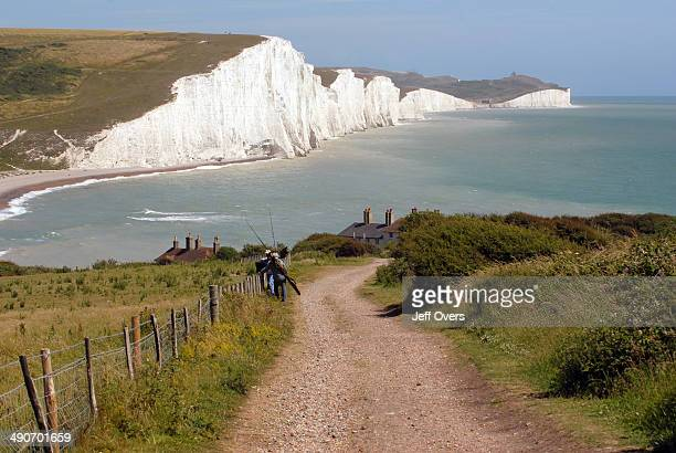 Two fishermen on the path to Cuckmere Haven from Seaford head in Seven Sisters Sussex England The Seven Sisters are a series of chalk cliffs by the...