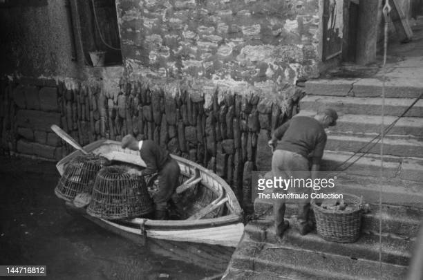 Two fishermen one with two lobster baskets in a rowing boat anchored to stone steps while the other fisherman prepares to lift a basket full of large...