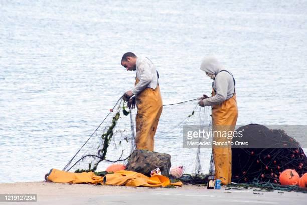 dos pescadores reparando redes de pesca en un muelle. - galicia fotografías e imágenes de stock