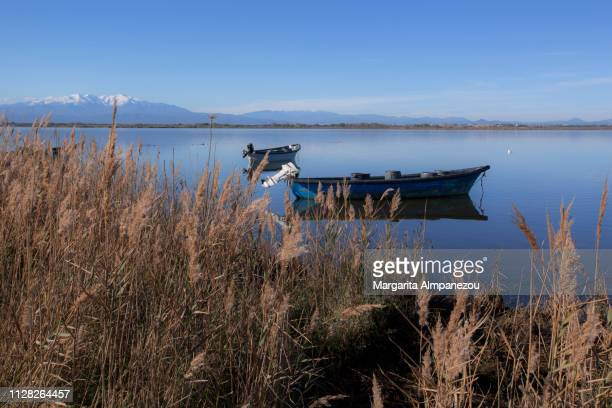 Two fishing boats on calm lake water with mountains at the background