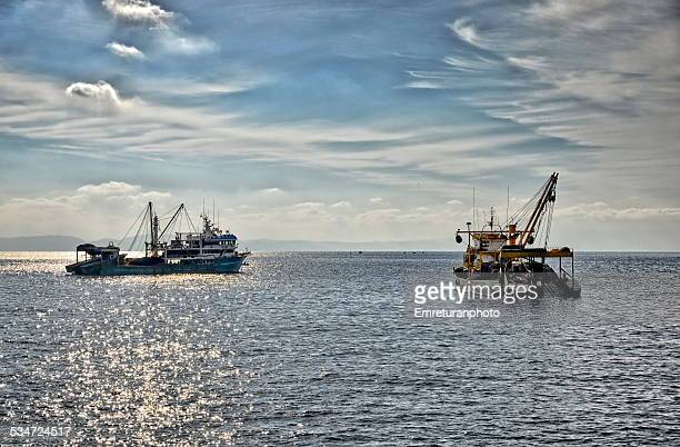 two fishing trawlers getting ready - emreturanphoto stock pictures, royalty-free photos & images