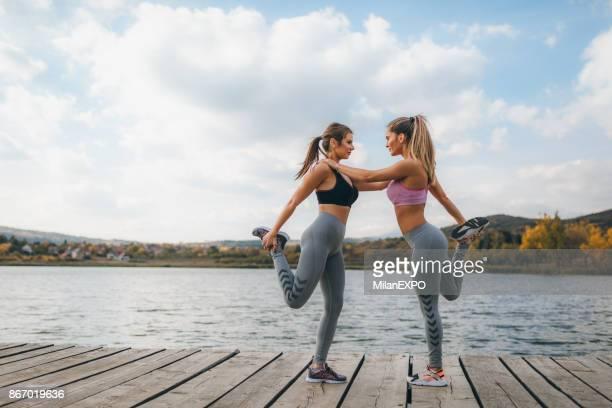 deux fit jeunes femmes échauffement et d'étirement à l'extérieur - bonne posture photos et images de collection