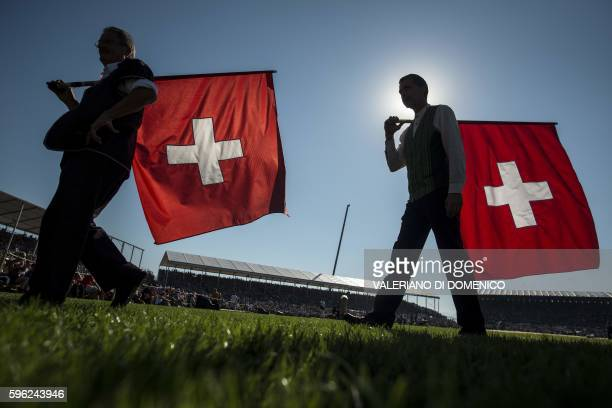 Two flag throwers walk past carrying Swiss national flags during the first day of the Federal Alpine Wrestling Festival on August 27 2016 in Payerne...
