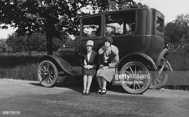 Two flappers sit on the running board of a car ca 1925