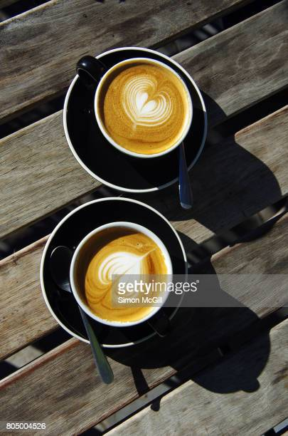 Two flat white milk coffee on a wood-slatted table at a sidewalk cafe in Canberra, Australian Capital Territory, Australia