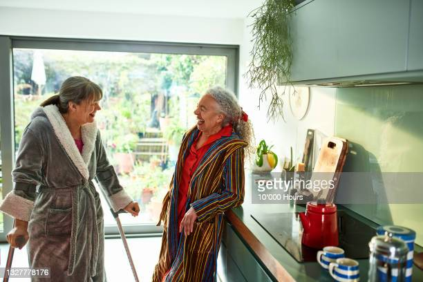 two flatmates laughing and smiling in kitchen - greater london stock pictures, royalty-free photos & images