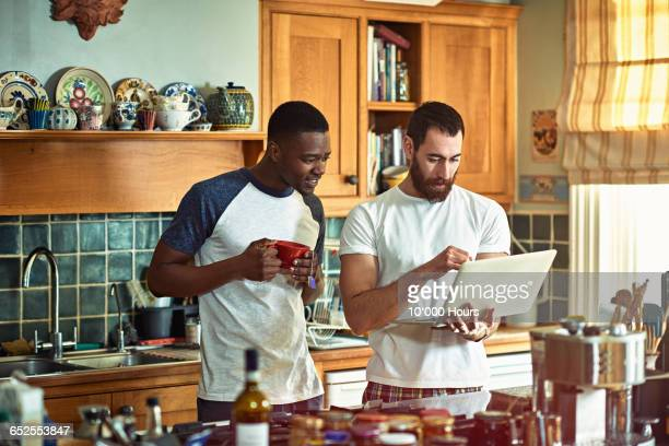 two flatmates looking at something on a laptop - roommate stock pictures, royalty-free photos & images