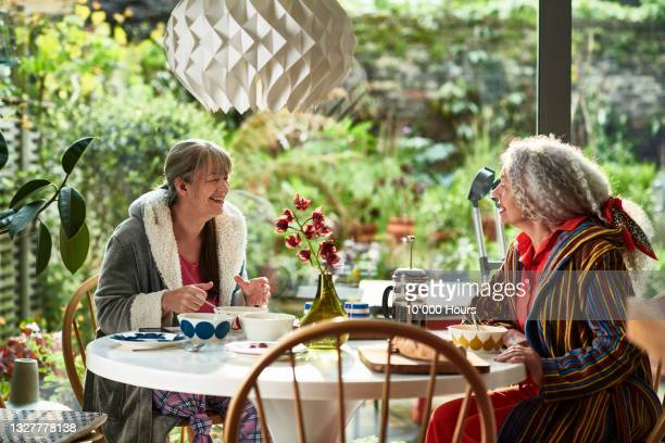 two flatmates smiling and chatting over breakfast in front of patio window - greater london stock pictures, royalty-free photos & images