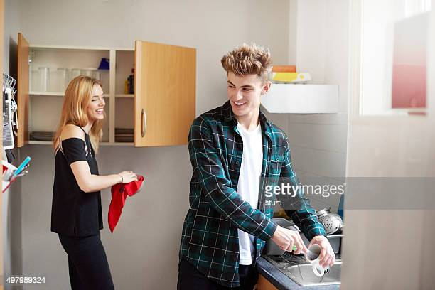 two flatmates washing dishes in the kitchen.