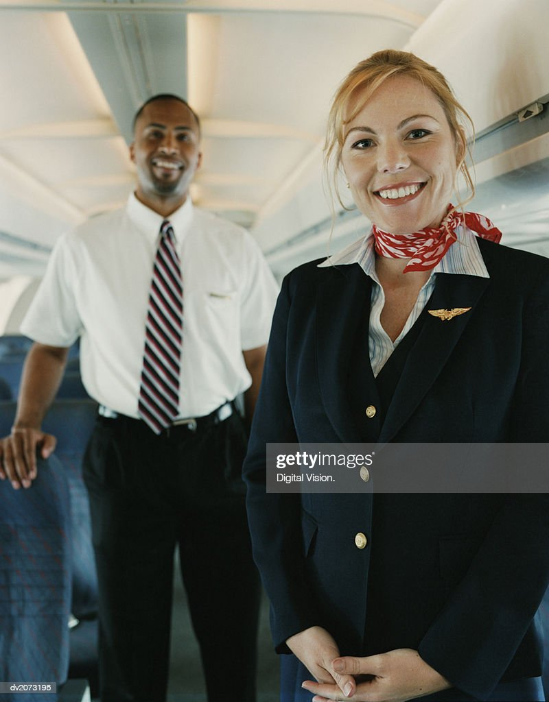 Two Flight Attendants Standing in the Cabin of a Plane : Stock Photo