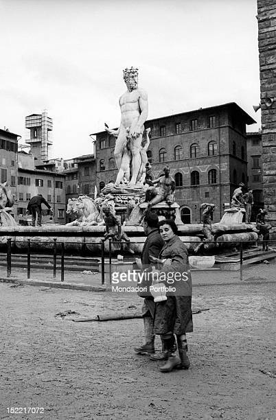 Two florentines walk by the Fountain of Neptune between the mud Florence 1966