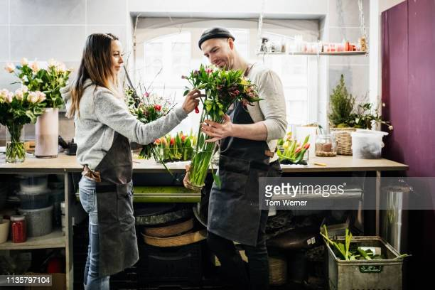 two florists preparing bouquet of flowers - retail place stock pictures, royalty-free photos & images