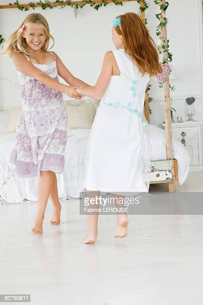 two flower girls playing in a bedroom - only girls stock pictures, royalty-free photos & images