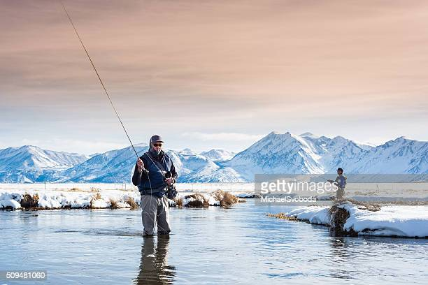two fly fisherman in the river during winter - fly casting stockfoto's en -beelden