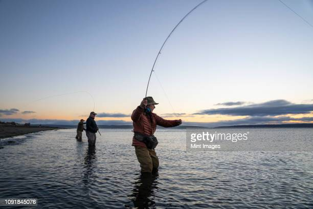 two fly fishermen cast for searun coastal cutthroat trout and salmon with their guide standing between them on a salt water beach  on a beach on the west coast of the usa - puget sound stock pictures, royalty-free photos & images