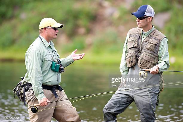Two Fly Fishers Discussing What The Fish Are Biting